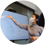 woman-at-work-pointing-to-screen-in-mask-and-grey-sweater